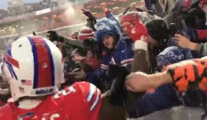 Bills players celebrate the win in the snow with their fans