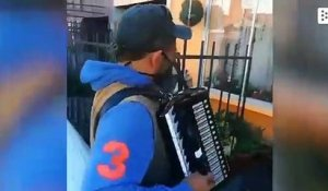 A Chilean plays the accordion in front of his parents' house to encourage confinement
