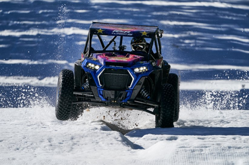 Le Polaris RZR XP Turbo S surfe sur une passe défoncée par un Pisten Bully Kässbohrer (engin de damage)